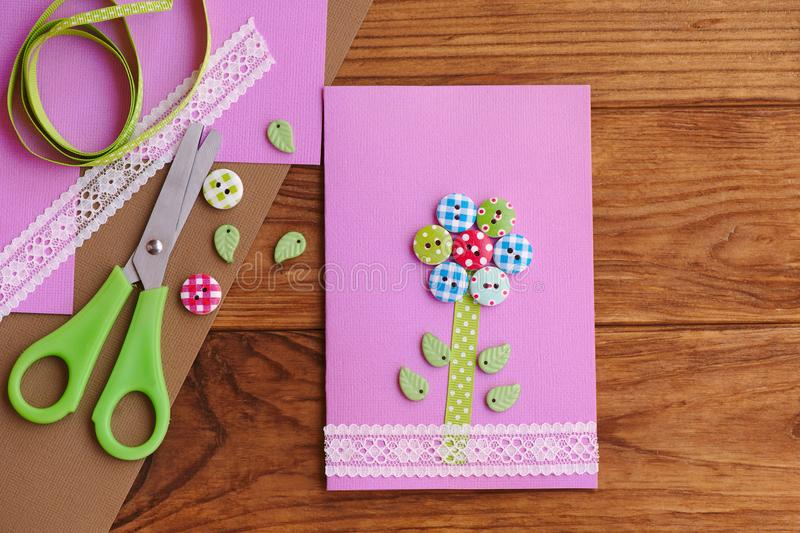 Greeting card with a flower from wooden buttons, decorated with lace. Birthday card for mom, Mother`s day diy. Tools and materials stock photo