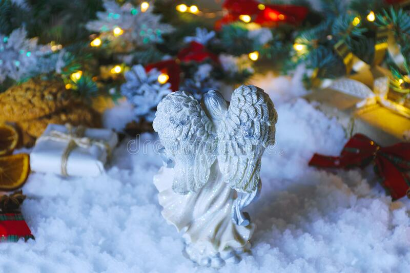 Greeting card for a gift. Angel in the snow on Christmas night. Gifts, spruce, cookies, lights, oranges, snowflakes and festive ti. Angel in the snow on stock photo