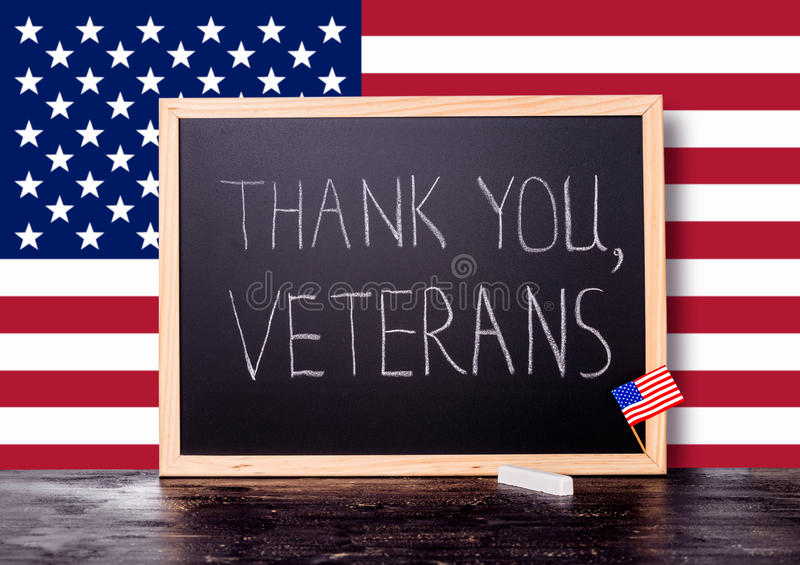 Greeting card of handwriting text thank you veterans is written. In chalkboard with flag United States and piece of chalk on craquelure background, close up stock photography