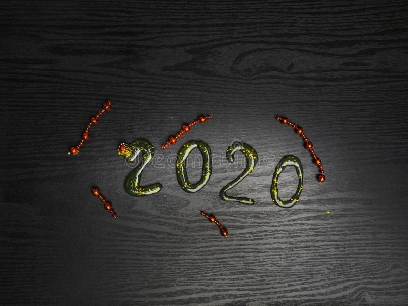Greeting card Happy New Year 2020. Beautiful Wide Angle creative holiday web banner or billboard with Golden sequins, red garlands. Inscription from slime 2020 stock photography