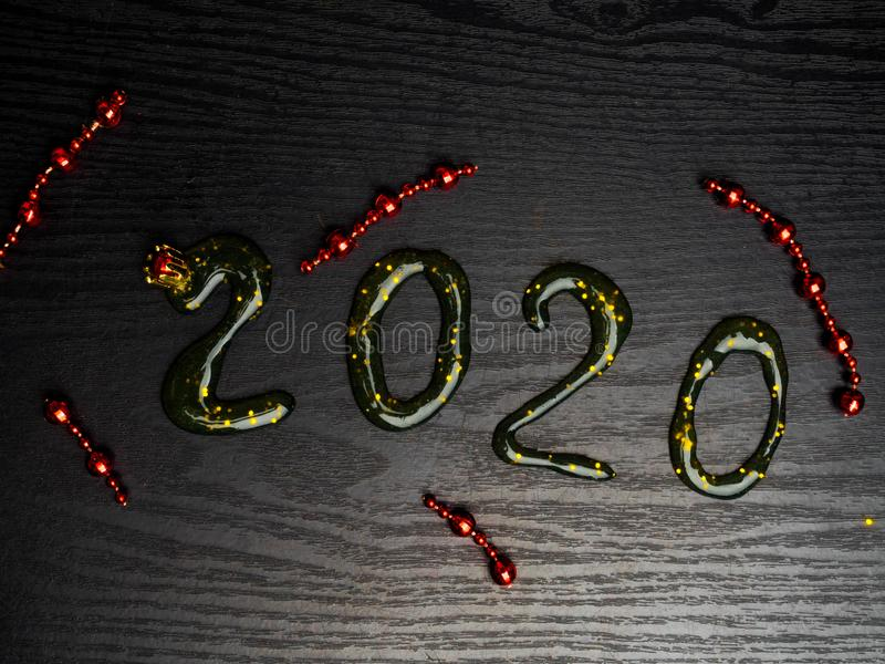 Greeting card Happy New Year 2020. Beautiful Wide Angle creative holiday web banner or billboard with Golden sequins, red garlands. Inscription from slime 2020 royalty free stock photography