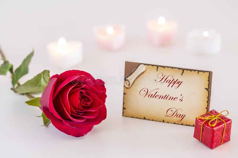 Greeting card with Happy Valentine`s Day text, single red rose, gift box, and candle light on white` royalty free stock image