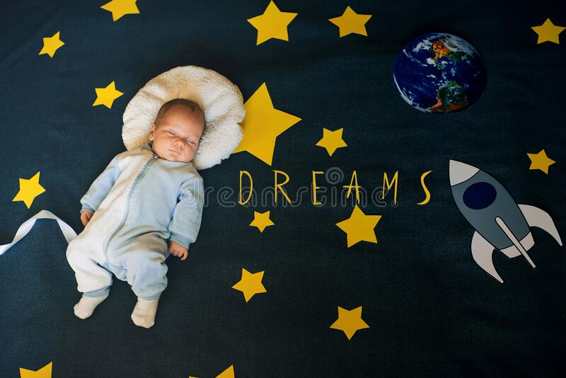 Greeting card with the inscription Dreams. Boy baby sleeping astronaut on the background of the starry sky royalty free stock photos