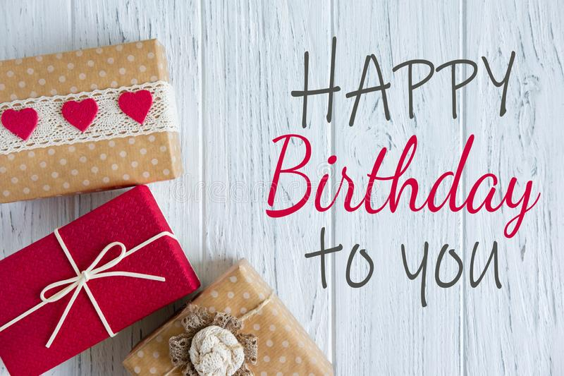Greeting card with the inscription happy birthday. A banner with a gift. Box with a gift on a light background with copy. Greeting card with the inscription royalty free stock images