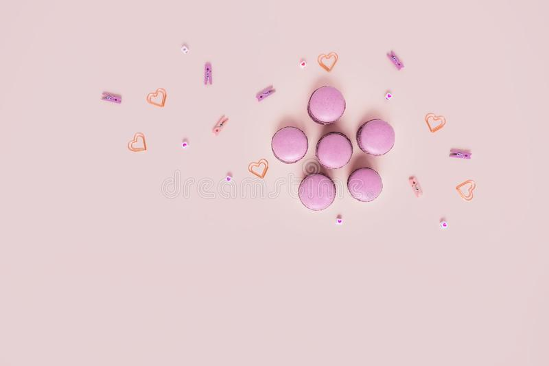 Greeting card with macaroons and hearts. Pink background with macaroons surrounded by hearts. Top view with space for your text stock image