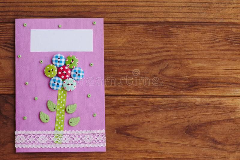 Greeting card made by a child for mothers day, fathers day, March 8, birthday. Paper card with a flower from wooden buttons. Mothers day cards to make in school stock images