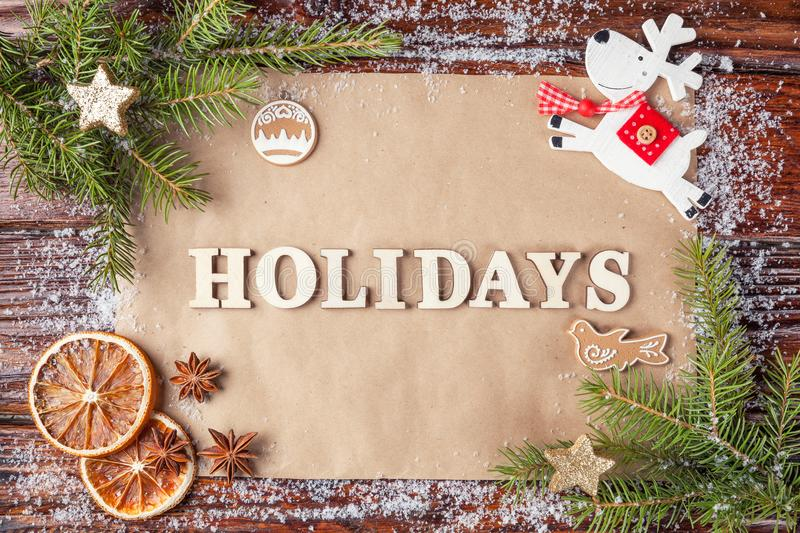 Greeting card for new year with inscription holidays, lined with wooden vintage letters. stock image