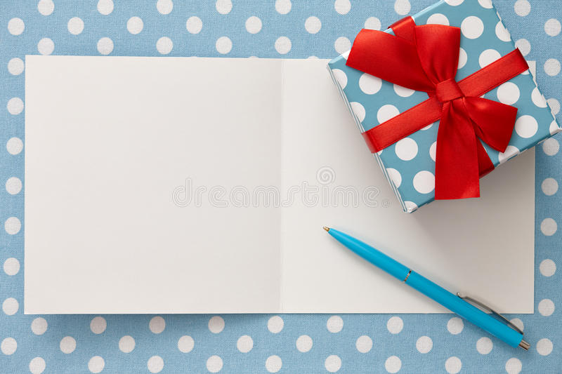 Greeting card with polka dot gift box and a pen stock images