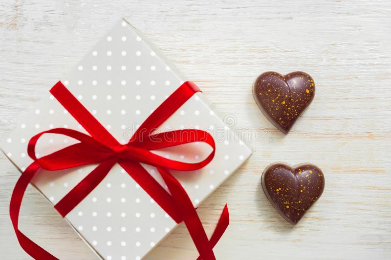 Greeting card for st valentines day. Chocolate sweets in heart shape and giftbox with red celebration ribbon on wooden background royalty free stock photo