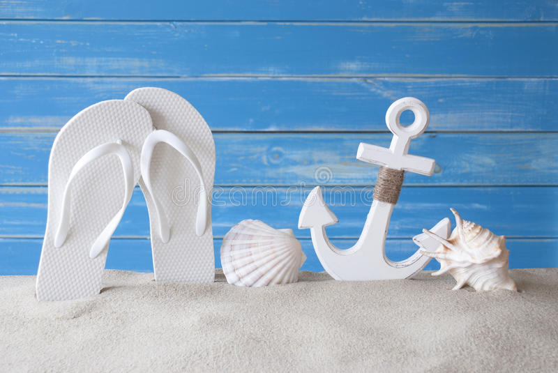 Greeting Card With Summer Decoration Like Anchor And Flip Flops. Chalkboard With German Text Schoenes Wochenende Means Happy Weekend. Blue Wooden Background stock photography