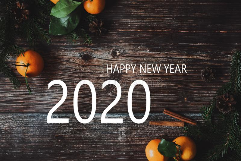 Tangerines with fir branches on a wooden background and the inscription Happy New Year 2020. Greeting card with tangerines with fir branches on a wooden royalty free stock images