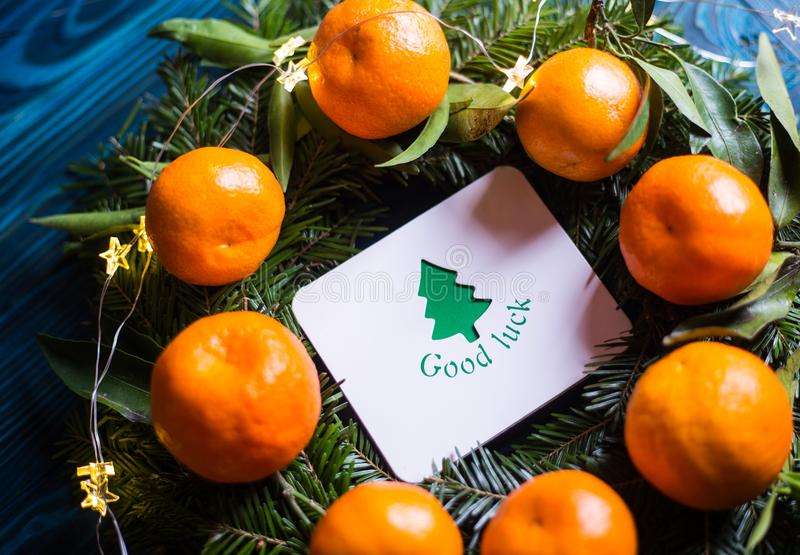Greeting card with wish `Good luck` surrounded with fresh mandarins and spruce branches with garland lights royalty free stock photo
