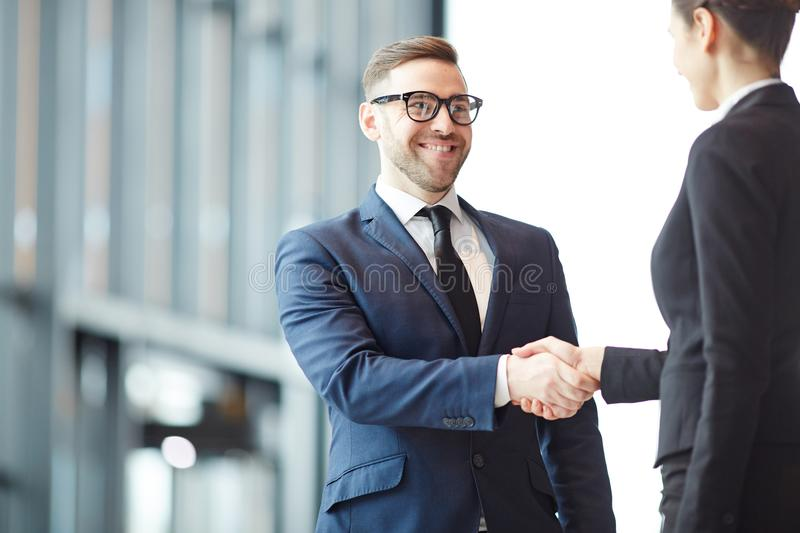 Greeting client. Elegant successful businessman greeting his new partner or client by handshake stock images