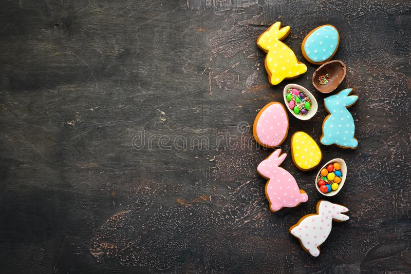 Greeting Easter Background. Easter gingerbread cookies and decorative colored eggs. On a brown background. Top view. Free copying space royalty free stock images