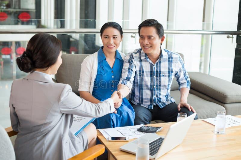 Greeting estate agent. Vietnamese couple greeting estate agent stock image