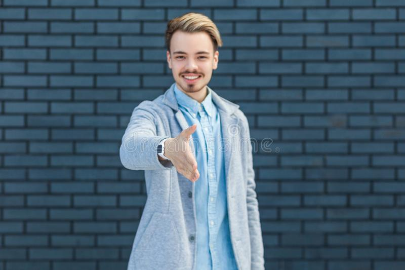 Greeting and hanshake. Portrait of happy handsome young blonde man in casual style standing, toothy smile and looking at camera. And giving hand to shake stock photos