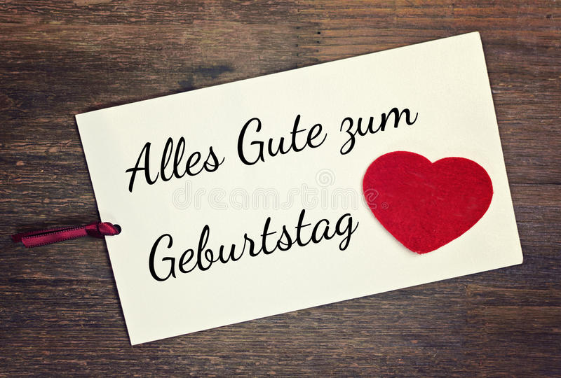 Greeting happy birthday. Greeting card with red heart german for happy birthday stock photos