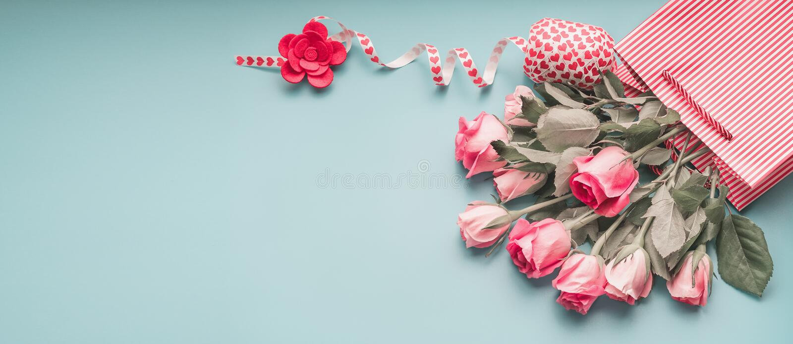 Greeting pink pale roses bunch in shopping bag with ribbon on turquoise blue background, top view. Copy space. Female holidays banner or template layout stock images