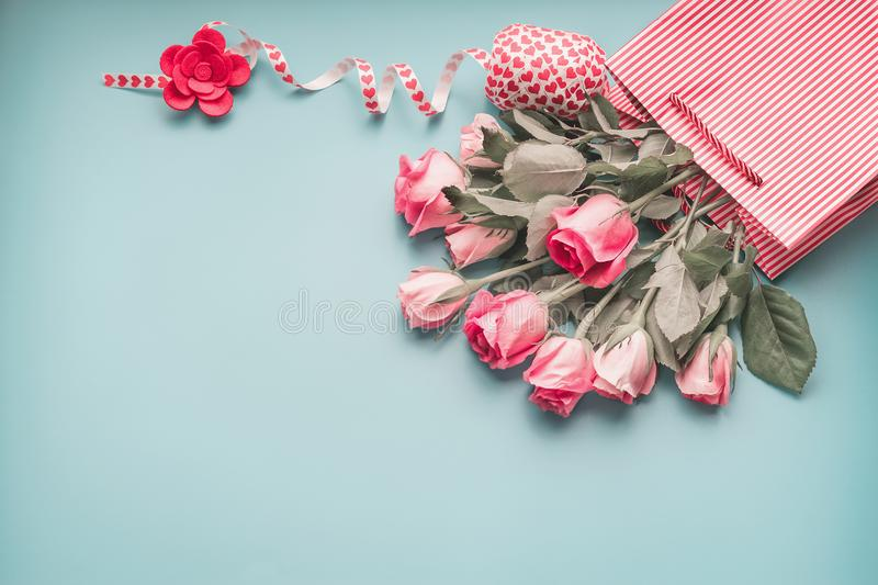 Greeting pink pale roses bunch in shopping bag with ribbon on turquoise blue background, top view. Copy space. Female holidays layout royalty free stock photos