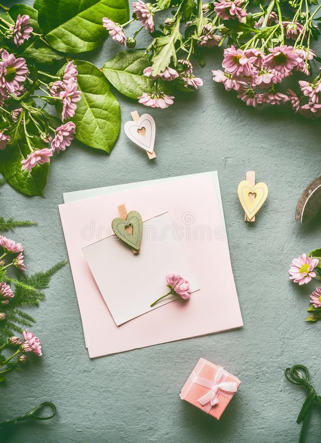 Greeting preparation with blank paper card mock up with heart and greeting preparation with blank paper card mock up with heart and gift box on florist desktop with green leaves and flowers top view flat lay mightylinksfo