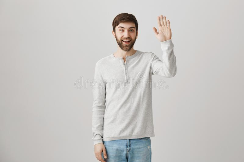 Greetings my friend. Indoor shot of friendly ordinary european male office worker waving at camera with broad smile royalty free stock photo