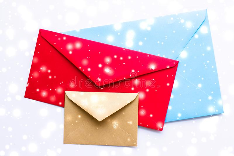 Winter holiday blank paper envelopes on marble with shiny snow flatlay background, love letter or Christmas mail card design. Greetings, postal service and royalty free stock photos