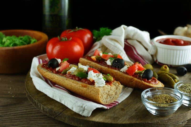 Grego Baguette Pizza com molho de tomate, Tomates triturados, Azeitonas verdes e negras, e Feta esmagada - com ingredientes fotografia de stock royalty free
