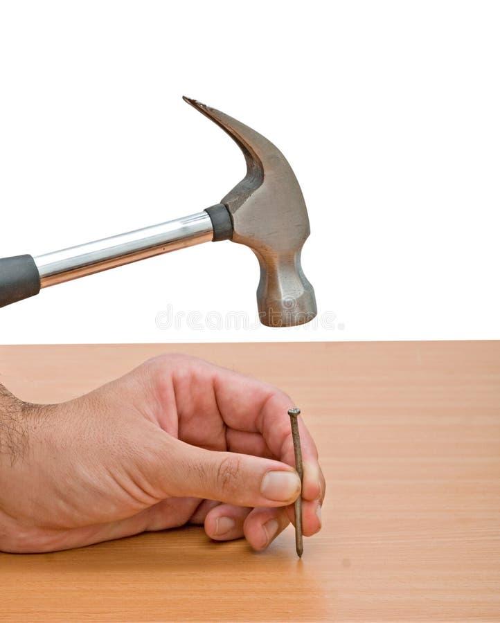 Greiferhammer und -hand mit Nagel stockbild