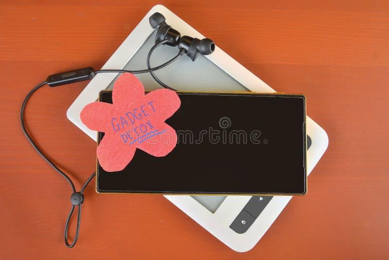 Grejdetoxbegrepp Digital böjelsebegrepp Mobiltelefon, eBook-avläsare och trådlös hörlurar med mikrofon på bordeauxbakgrund modern arkivbilder