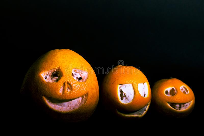 Grejpfruty, tangeryny i pomarańcze są izolowane na czarnym tle w postaci dyni halloweenowej Straszna twarz jest wyrzeźbiona zdjęcia stock