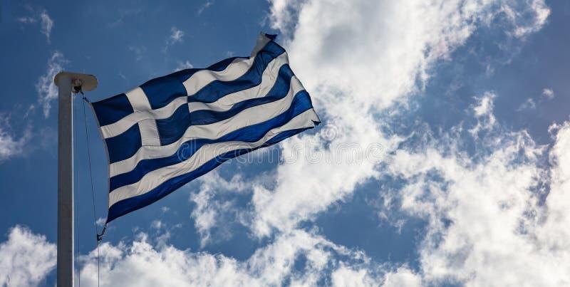 Grek flaga na flagpole falowaniu na niebieskiego nieba tle zdjęcie stock
