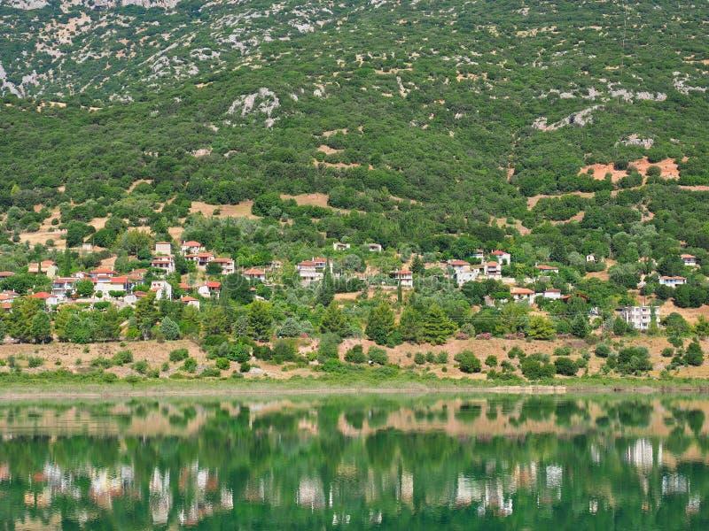 Grekisk by för berg reflekterad i sjövatten royaltyfri fotografi