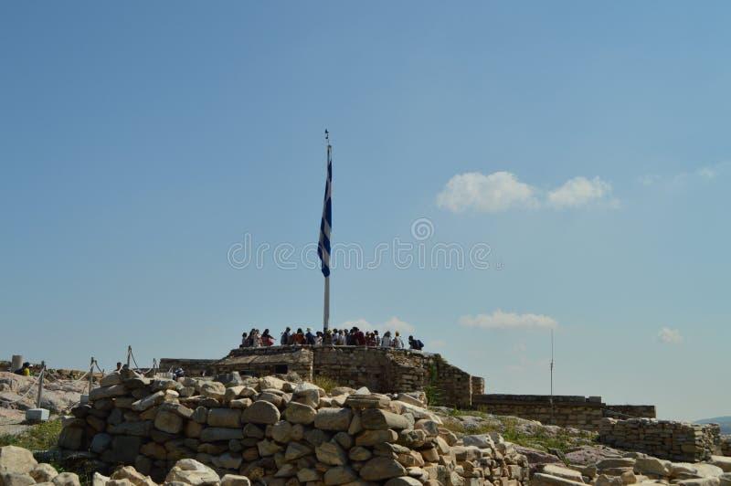 Grekisk flagga nära en av utkik i akropolen av Aten I Acroplisen av Aten Historia arkitektur, lopp, Archeolo fotografering för bildbyråer