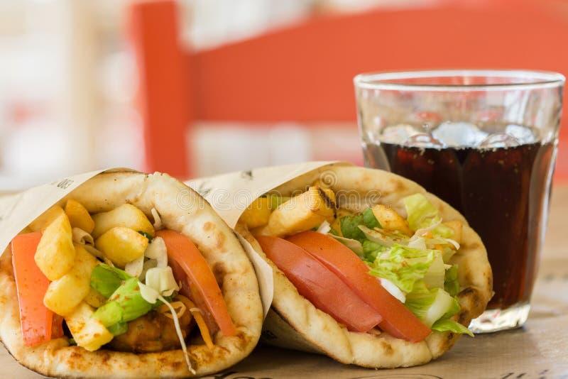 Grekisk kokkonst, souvlaki, gyroskoppitabröd och ett exponeringsglas av drinken I krogen i Grekland fotografering för bildbyråer