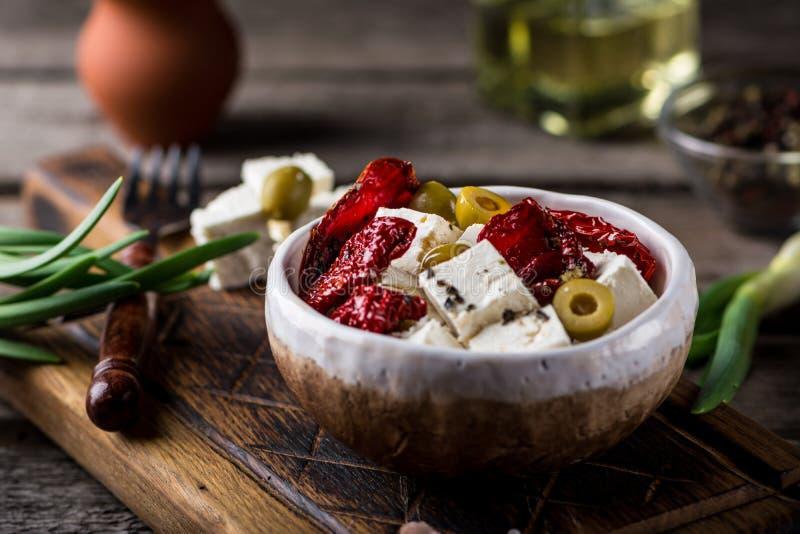 Grekisk ostfeta med örter och oliv, sundried tomater Bulgarisk ost Feta i olja Olove olja Selektivt fokusera royaltyfri foto