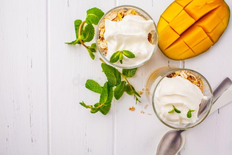 Grekisk parfait för yoghurtmangogranola i ett exponeringsglas på vita trälodisar arkivfoto