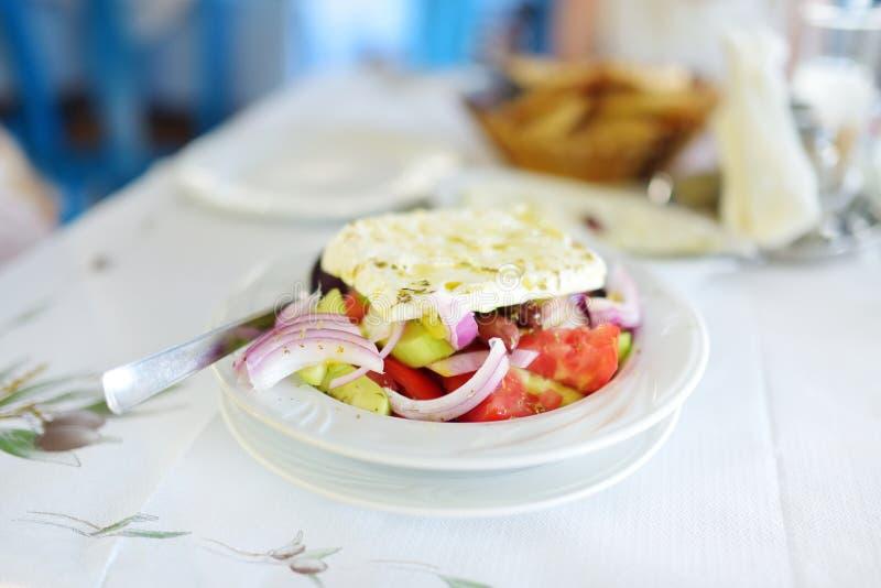 Grekisk sallad av den nya gurkan, tomaten, söt peppar, grönsallat, den röda löken, fetaost och oliv med olivolja som överträffas  royaltyfria foton