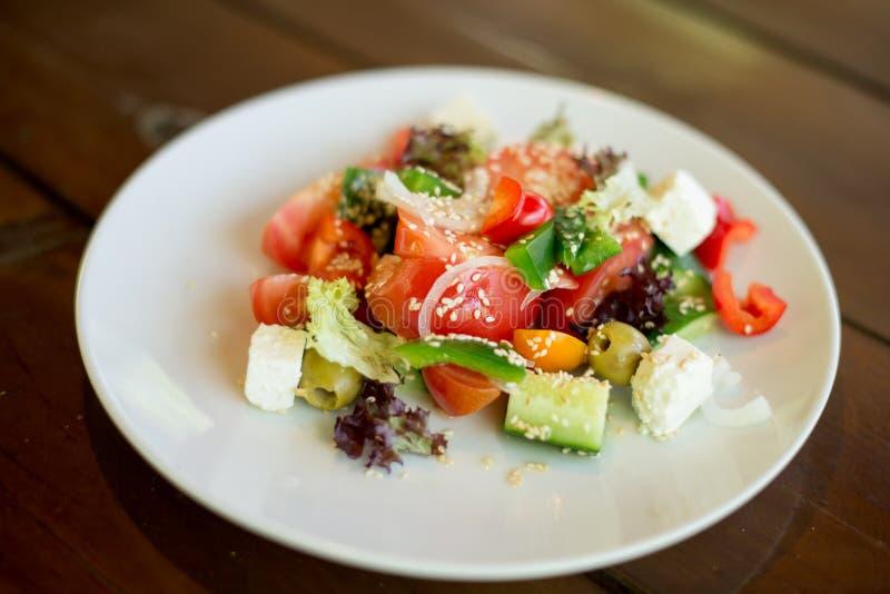 Grekisk sallad av den nya gurkan, tomaten, söt peppar, grönsallat, den röda löken, fetaost och oliv med olivolja Sund mat som är  royaltyfria foton