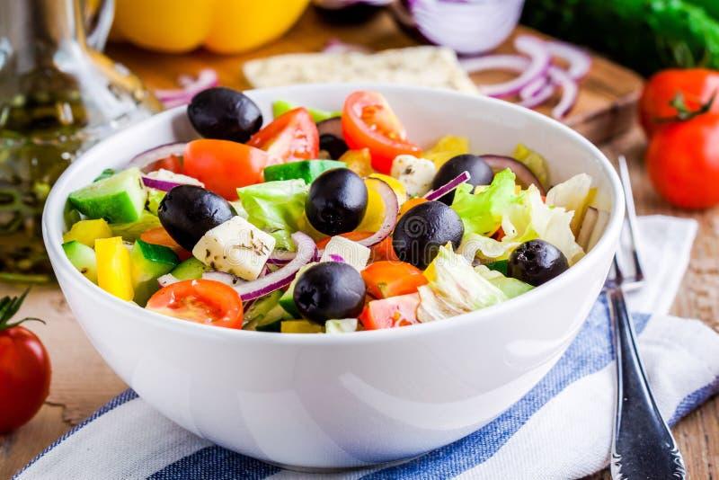 Grekisk sallad av organiska tomater, gurkan, den röda löken, oliv och fetaost arkivbild