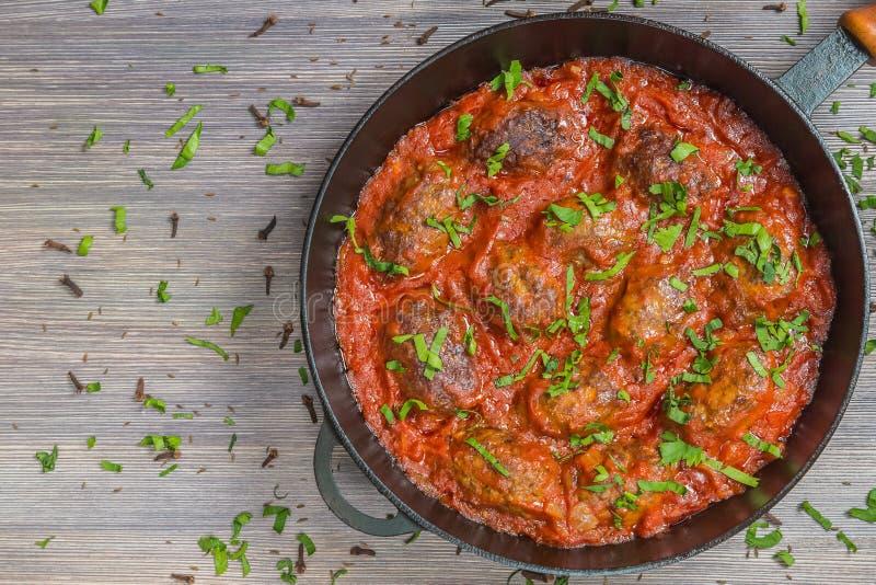 Grekisk soutzoukakia små pastejerna i tomatsås i pannan close upp övre sikt Kopia-utrymme arkivbilder