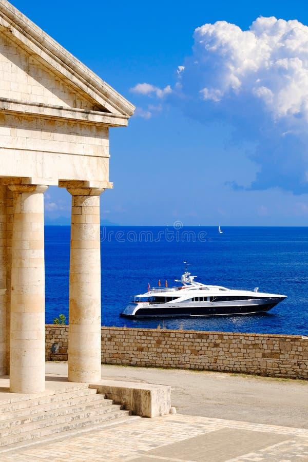 Grekisk symbolpanteon nära havet med yachten arkivbild