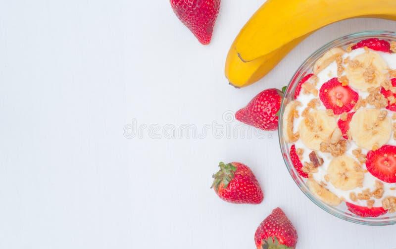 Grekisk yoghurt med mysli, jordgubbar och bananen arkivbilder