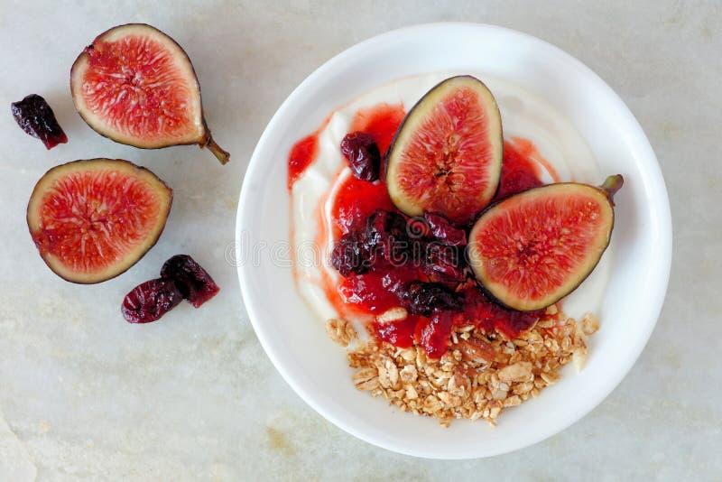 Grekisk yoghurt med söta fikonträd, bär och granola, över marmor royaltyfri fotografi