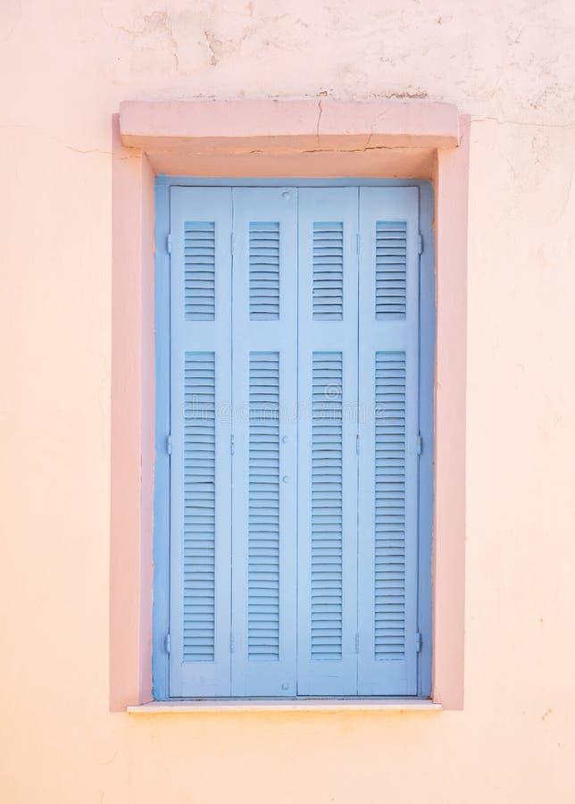 Grekland Kea ö Det traditionella träfönstret stänger med fönsterluckor blå pastellfärgad färg på den rosa målade väggen i huvudst arkivbilder
