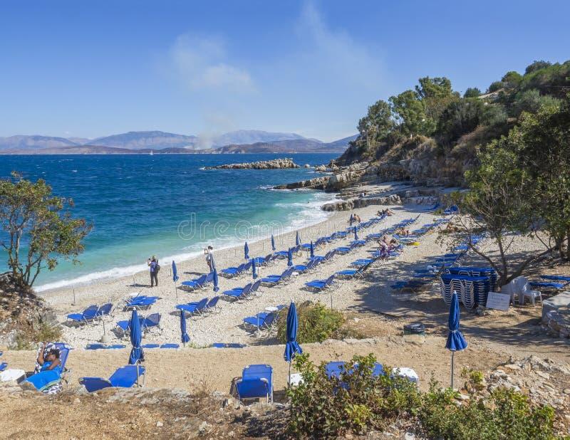 Grekland Korfu, Kassiopi september 28, 2018: Sikt av Bataria den vita sandstranden med blåa sunbeds och turist- folk på royaltyfria foton