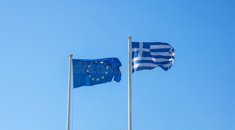 Grekland och EU Flaggor för grekisk och europeisk union som vinkar på klar blå himmel royaltyfria bilder