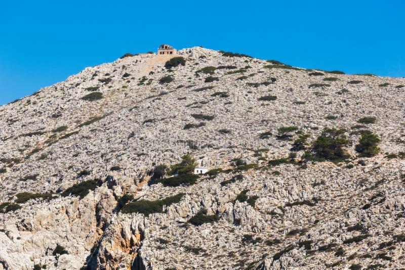 Grekland Panormitis Berg och byggnader på ingången till fjärden royaltyfria bilder