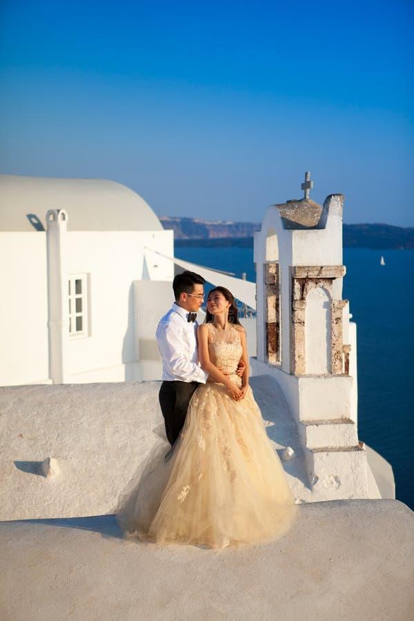 Grekland Santorini, Oia September 16, 2014: ett par av nyligen gift folk i härlig dress som tycker om deras bröllopsresamånader arkivfoto