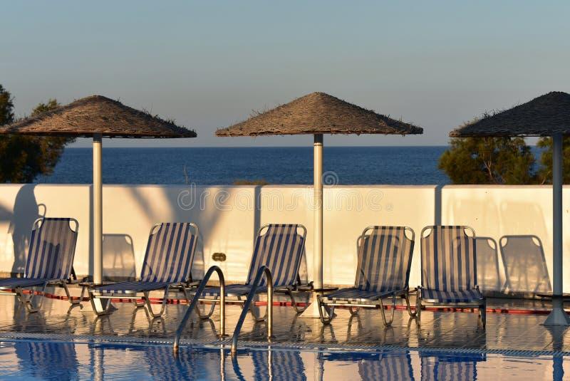 Grekland Santorini, solsängar av en simbassäng royaltyfria bilder