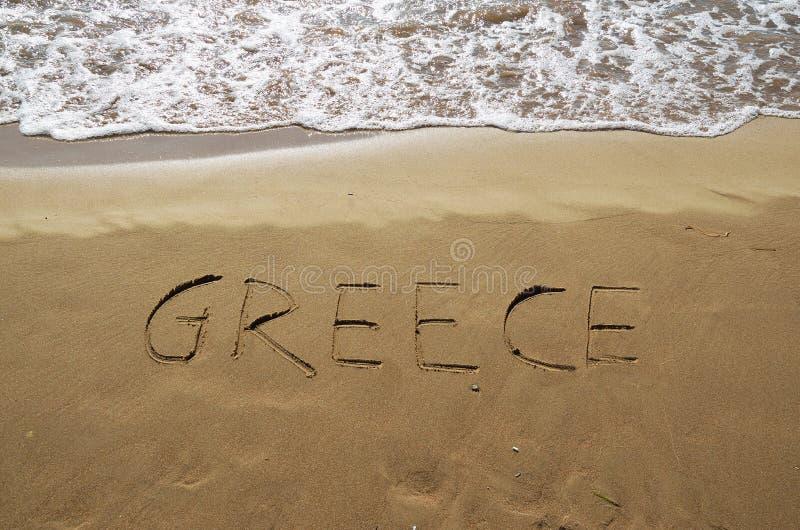 Grekland som är skriftlig i sand arkivbild